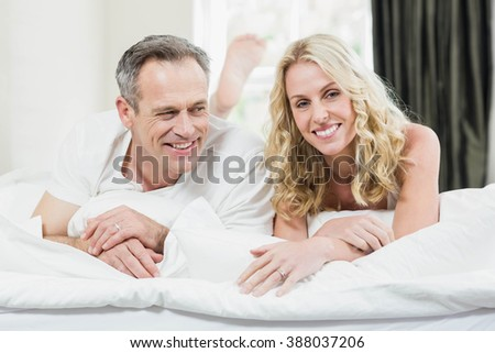 Cute couple lying on their bed in their room - stock photo