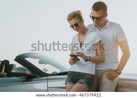 Cute couple of tourists man and woman consulting a smartphone gps in the street searching locations they need
