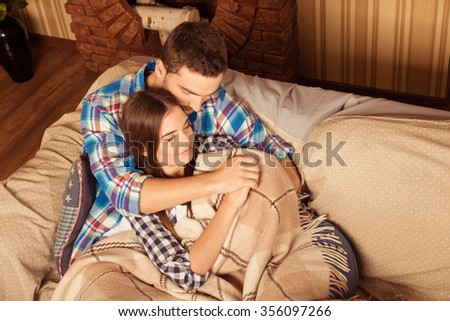 Cute couple on sofa under the plaid - stock photo
