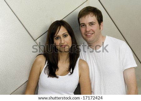 Cute couple posing in white tops outside against wall - stock photo