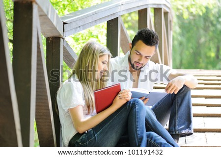 Cute couple reading boot while sitting on a wooden bridge outdoors - stock photo