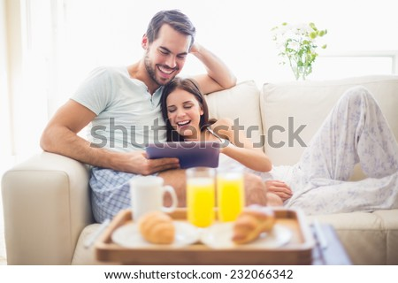 Cute couple relaxing on couch with tablet at breakfast at home in the living room - stock photo