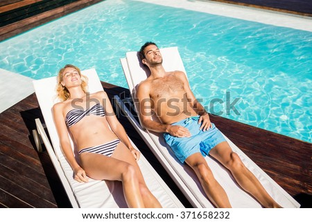 Cute couple relaxing on deckchairs by the pool - stock photo