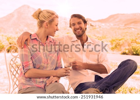 Cute couple sitting in the garden enjoying wine together on a sunny day - stock photo