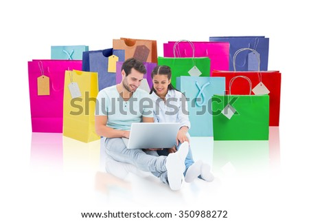 Cute couple sitting using the laptop against white background with vignette - stock photo