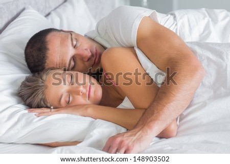 Cute couple sleeping and cuddling in bed at home in bedroom - stock photo