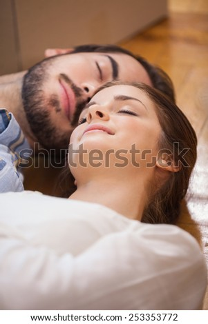 Cute couple sleeping on the floor in their new home - stock photo