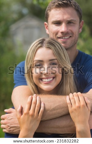 Cute couple smiling at camera at home in the garden