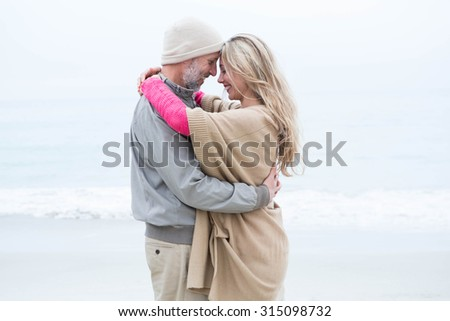 Cute couple standing and holding each other at the beach