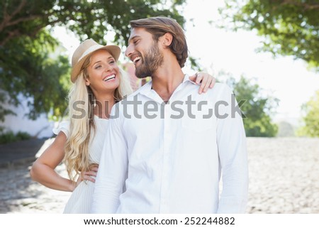Cute couple standing and smiling on a sunny day in the city