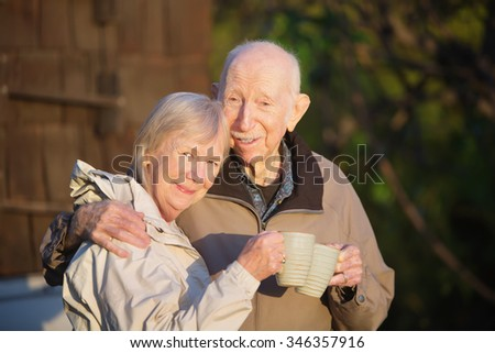 Cute couple standing outdoors holding coffee mugs - stock photo