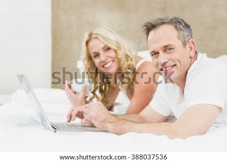 Cute couple using laptop in bed in their bedroom - stock photo
