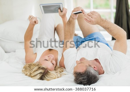 Cute couple using tablet and smartphone in bed - stock photo