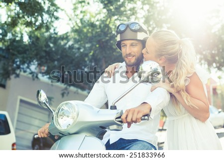 Cute couple with their scooter on a sunny day in the city - stock photo