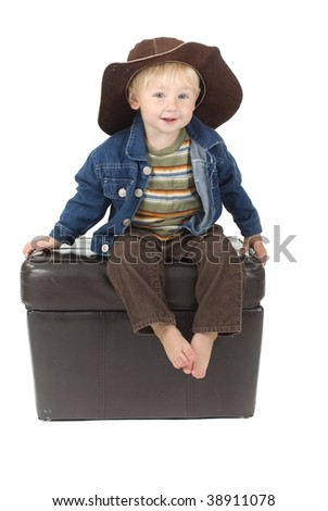 cute cowboy toddler sits on stool - stock photo