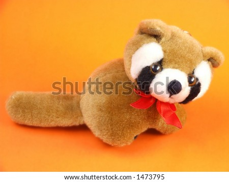 Cute cuddly brown raccoon toy. Brown raccoon - small toy animal on an orange background. - stock photo