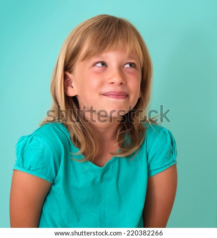 Cute cunning little girl isolated on turquoise background. Human emotion facial expression. - stock photo