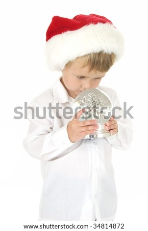 Cute curious toddler wearing Santa Hat looks closely at snowflakes in snow globe nose touches glass  - Christmas the - stock photo