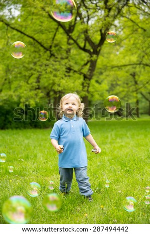 Cute curly baby with soap bubbles children playing running Child playing outdoors in the flowering trees in spring summer garden.  Springtime or summertime. Boy in spring summer landscape background.  - stock photo
