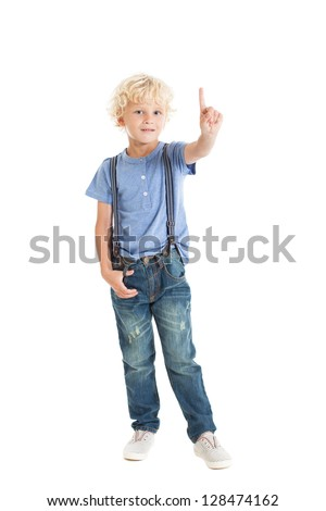 Cute curly blond boy wearing a blue shirt, suspenders, jeans and sneakers, showing the index finger. Studio shot, isolated on white background. - stock photo