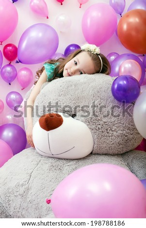 Cute curly girl posing lying on big plush bear - stock photo