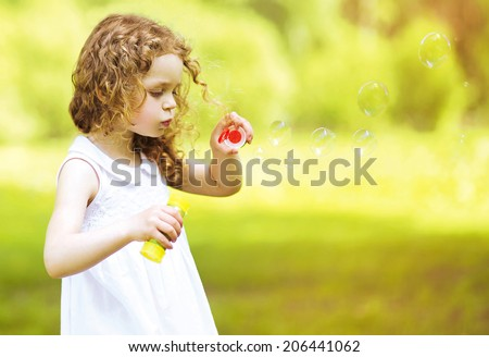 Cute curly little girl blowing soap bubbles outdoors in summer day - stock photo