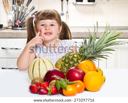 Cute curly little girl eating fresh fruit - stock photo