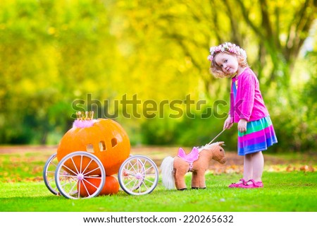 Cute curly little girl playing Cinderella fairy tale holding a magic wand next to a pumpkin carriage having fun in an autumn park at Halloween - stock photo
