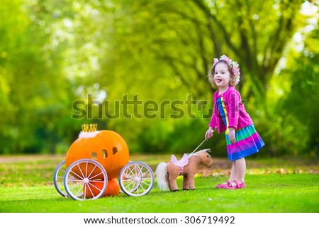 Cute curly little girl playing Cinderella fairy tale holding magic wand next to a pumpkin carriage in autumn park at Halloween. Kids trick or treat at pumpkin patch. Family with children carving. - stock photo
