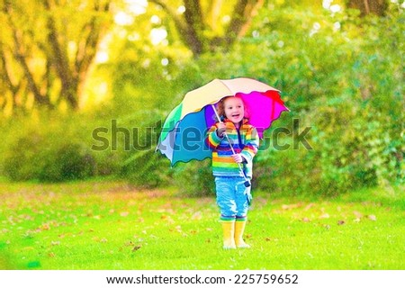 Cute curly toddler girl in yellow waterproof suit and boots holding colorful umbrella playing in the garden by rain and sun weather on a warm autumn or summer day  - stock photo