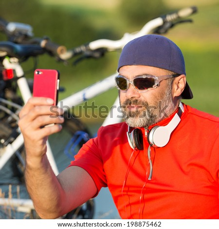 Cute cyclist relaxing after riding his bike using cell phone on nature lake and green meadow background. focus on face