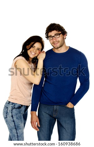 Cute dark haired couple stood together smiling at the camera isolated on a white background