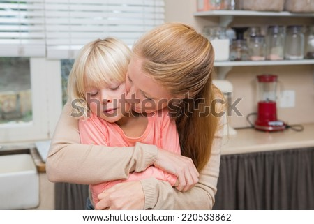 Cute daughter and mother hugging at home in the kitchen - stock photo