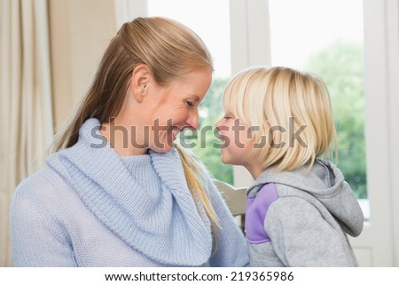 Cute daughter and mother together at home in the living room