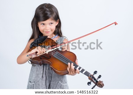 Cute daughter playing violin - stock photo