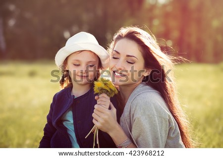 Cute daughter present her mother the yellow flowers and happy mother smelling its with enjoying face on summer background - stock photo