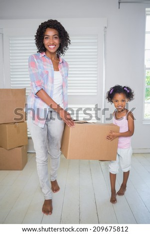 Cute daughter unpacking moving boxes with her mother in their new home - stock photo