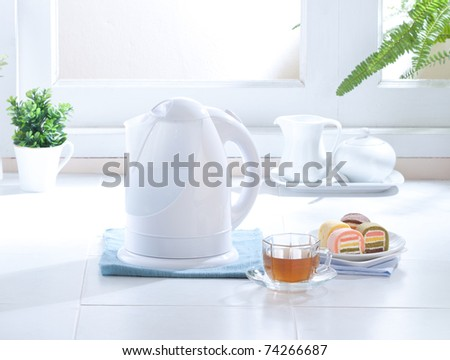 Cute design of the electric kettle in the kitchen interior - stock photo