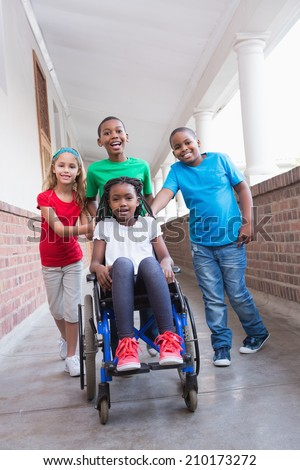 Cute disabled pupil smiling at camera in hall with her friends at the elementary school - stock photo