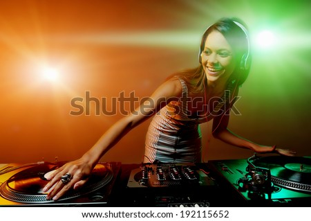 Cute dj woman having fun playing music on vinyl record deck at club party nightlife lifestyle - stock photo