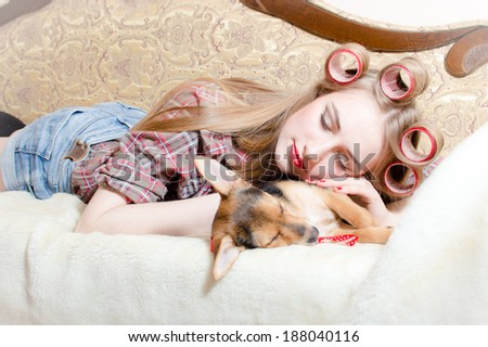 cute dog and blond beautiful pinup girl with red lips curlers in her hair lying in bed sleeping picture - stock photo