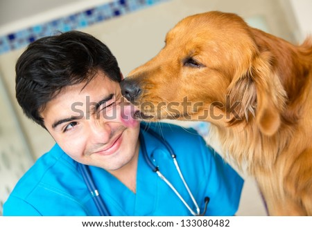 Cute dog giving a kiss to the vet after a checkup - stock photo
