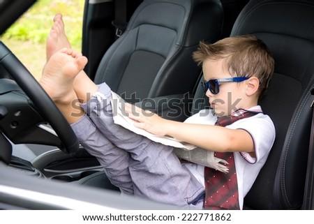 Cute driver reads newspaper in car - stock photo