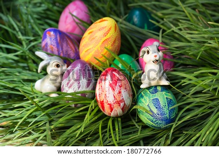 Cute Easter bunnies and eggs hiding in between the green grass