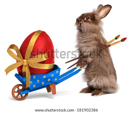 Cute Easter bunny rabbit with a little blue wheelbarrow and a red Easter egg with a golden ribbon, isolated on white, CG and photo - stock photo