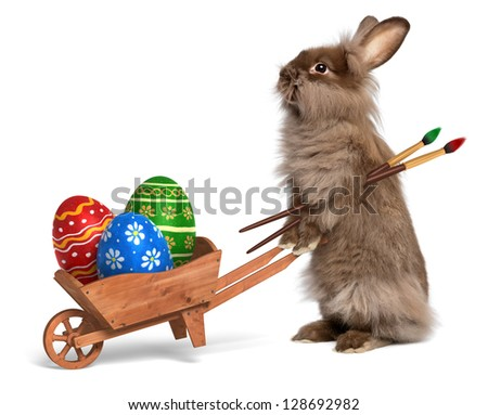 Cute Easter bunny rabbit with a little wheelbarrow and some painted Easter eggs, isolated on white, CG+photo - stock photo