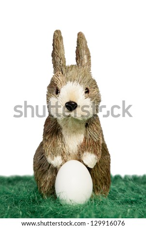 Cute Easter bunny standing on green grass with one white egg - stock photo