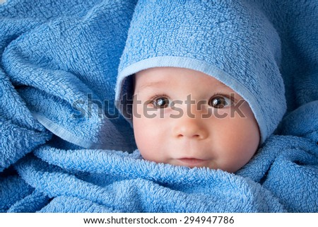 Cute eight month old baby wrapped in a towel - stock photo