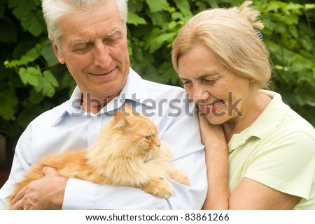 cute elderly couple with a cat at nature - stock photo