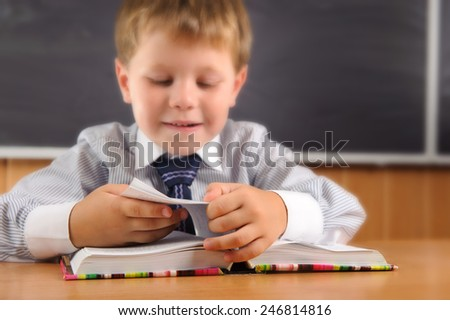 Cute elementary aged boy sitting at the desk with books